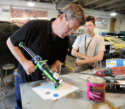 """Scott Rex of Rex Marketing, shows Alex Dain some of his dent repair product at the auto classes at CTEC.<br /> For more photos and a video from CTEC, go to  <a href=""""http://www.dailycamera.com"""">http://www.dailycamera.com</a><br /> Cliff Grassmick / May 3, 2012"""