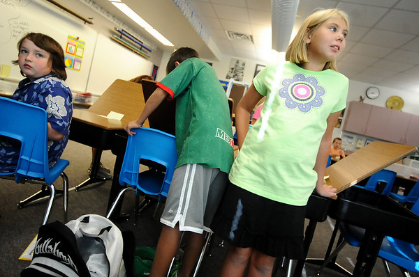 Fourth graders, left to right, Tony Sanchez, Diego Perez-Antillon and Nicole Sittner wait for direction from their fourth-grade teacher at the first day of school at Crestview Elementary School on Thursday.<br /> Photo by Marty Caivano / The Camera / August 20, 2009