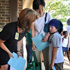 Kai Dewey, 7, right, clings to his mother, Reiko, as second-grade teacher Virginia Pool tries to persuade him to let go at the first day of school at Crestview Elementary School on Thursday.<br /> Photo by Marty Caivano / The Camera / August 20, 2009