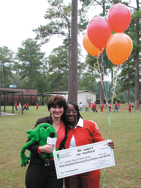 Anne Cordeiro, the director of communications at Coastal Electric Cooperative, congratulates Celestine Barrett on her win. With them is Froggie, who travels often to schools.