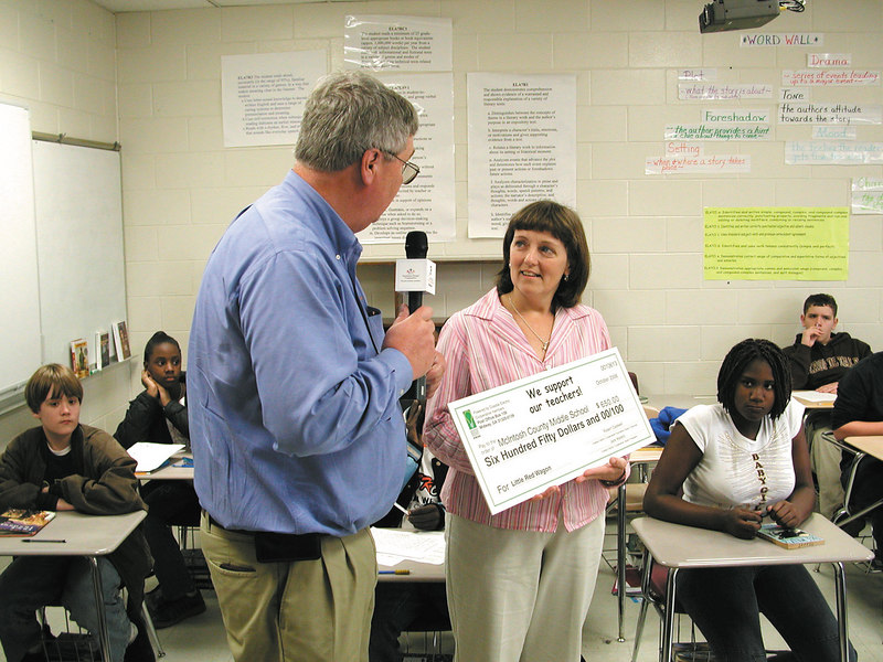 Cindy Jarriel at McIntosh County Middle School listens to CEO Whit Hollowell explain how Bright Ideas is a part of Coastal Electric's commitment to community, a core value of Touchstone Energy Cooperatives.