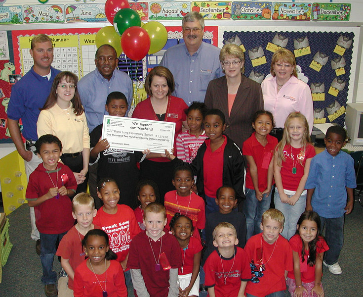 Frank Long Elementary teacher Becky Busby is surrounded by members of the Bright Ideas Prize team, employees and directors of Coastal Electric Cooperative and its Foundation, and her students. Busby won a $1,270 grant for Microscope Mania.