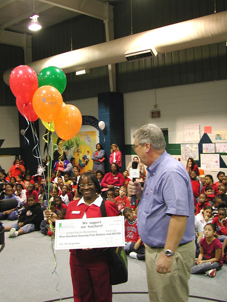 Celestine Barrett, a teacher at Jordye Bacon Elementary, was surprised at an unrelated school assembly, with news that she had won a $975 grant to create a student newspaper at her school.