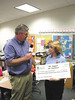 Coastal Electric CEO Whit Hollowell congratulates Patricia Moody on winning a $1,960 grant for her project, Natural Resources Rock!