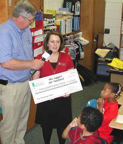 Frank Long Elementary School teacher Becky Busby won a $1,270 grant to buy high-tech microscopes for her students. Coastal Electric CEO Whit Hollowell asks her about the project while students look on.
