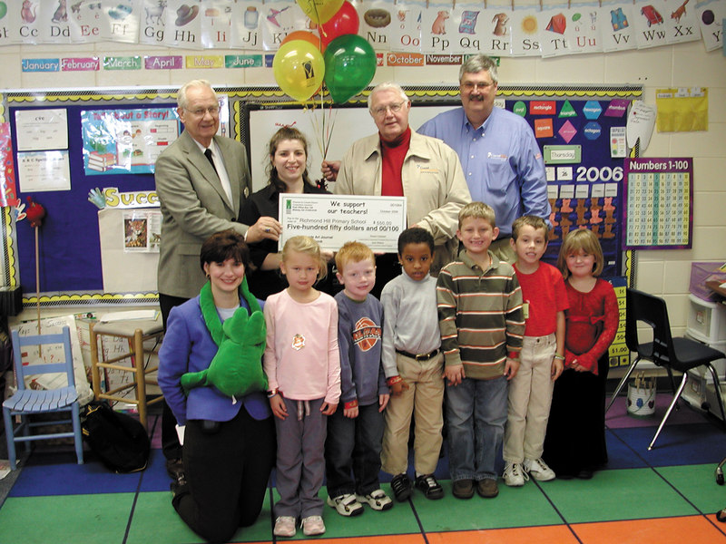 Jimmy Estes, Vice-Chairman of the Coastal Electric Cooperative Board of Directors, left, Bob Caldwell, Chairman of the Foundation Board, and Coastal Electric CEO Whit Hollowell congratulate Richmond Hill Primary School teacher Aura Welch on winning a Bright Ideas Grant. Also pictured are Anne Cordeiro, who manages the Bright Ideas program, and students from Welch's class.