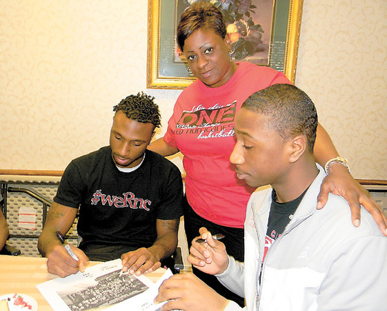 Dan Irwin/NEWS<br /> Angela Dennis, a cook at The Haven Convalescent Home, welcomes her sons Malik Hooker, left, and Marquel Hooker to the facility yesterday, where they were autographing New Castle High basketball team photos for residents. The two were members of the squad, which recently won its first-ever state championship.