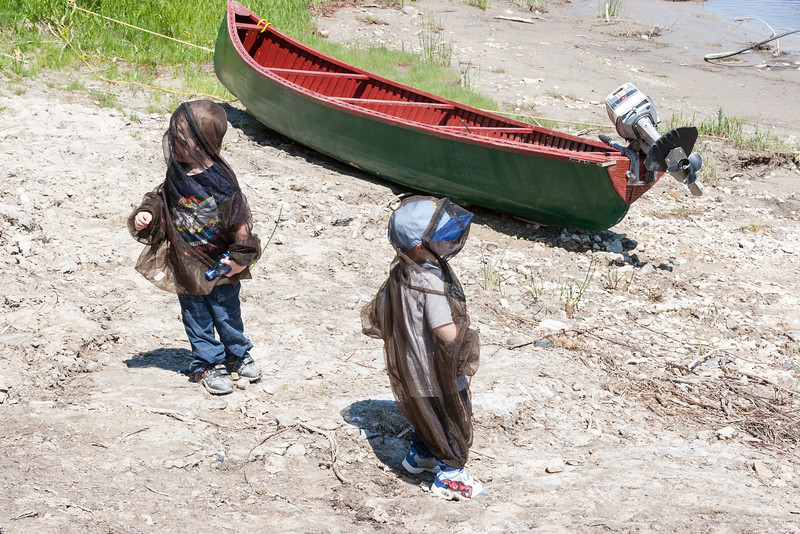 Two children in bug suits wait for the canoes to return. 2006 June 13