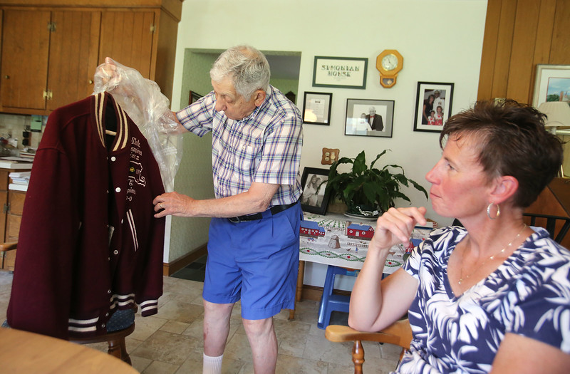 Chelmsford High School Alumni Association executive director George Simonian, with a 1987 Chelmford High Super Bowl year jacket, and the organization's new fundraiser, Heather Linstad, who is a CHS alum and CHS softball coach. Simonian hopes items he's been saving like the jacket will eventually be able to be moved to the CHSAA's own building. (SUN/Julia Malakie)