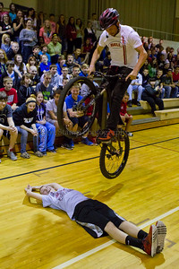 Spring Hill Junior High 7th and 8th grade students watch as Chris Clark, a bicycle stunt rider leaps over volunteer and fellow student Paul Stubbs on Friday April 27,  2013, Springfield Township, Ohio.   Troopers from the Ohio State Highway Patrol and members of the Fraternal Order of Police lodge #157 have combined to cover the cost of the event. Lew Stamp Photography.