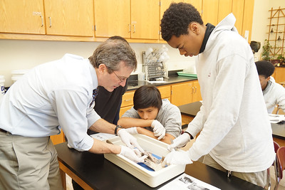 Biology teacher Chris Cogswell and some of his students discuss what the students discovered during their dissection of a dogfish shark.