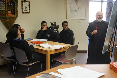 Br. Maximilian Buonocore and his tutees enjoying a laugh as he provides extra help to science and math students in the Radel Library.