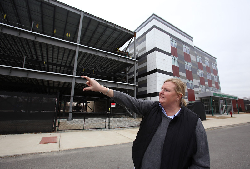 School director Laurie Hodgdon, and high school extension under construction at Collegiate Charter School of Lowell. (SUN/Julia Malakie)