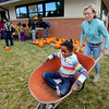 Catriona Dowling pushes her daughter, Angelina Dowling-Davis, in wheelbarrow during the harvest celebration on Saturday.<br /> This year's  Columbine Elementary  garden harvest event  celebrated the students' work and learnings in the garden. Participants had healthy food, made  artwork for the garden, painted pumpkins and enjoyed being together as a school community.<br /> Cliff Grassmick  / October 20, 2012