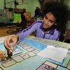 "Kylie Merritt, 10, demonsrates her board game titled, ""Little Pet Shops to the Store"" at the 20th Annual Science, Math and Technology Fair at Crocker Elementary School on Tuesday."
