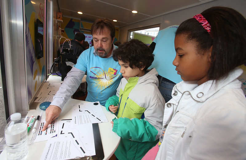 MilliporeSigma's mobile science lab, the Curiosity Cube, visits the Moody Elementary School in Lowell. From left, Sam Souza of Lowell, customer service manager at MilliporeSigma, explains how to fill in gaps in a line representing a nerve, so a mini-robot will follow it, to Andres Cuartes and Arismel Rosario. (SUN/Julia Malakie)