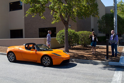 A Tesla Roadster is inspected by Alan Gaynor '67, Whitney Flynn '07, and David Liddle.