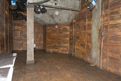 The first production space developed was this former ammunition-storage vault.  All the wall-mounted features are set dressing.  The loops and attachment points on the ceiling and posts are for real and very sturdy.  The floor, however, while it looks like the wood in the walls, is cleverly decorated foam padding, out of consideration for models spending a lot of time on their knees.