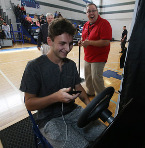 Safe A Life Tour visits Nashoba Tech to demonstrate to students the danger of distracted driving and texting and driving. Save A Life tour manager Clay Martin, rear, watches Peter Manzelli, 16, of Chelmsford, do the simulation.  (SUN/Julia Malakie)