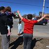 Englesby Elementary School teachers hold a parade of 30 cars with signs through their students' neighborhoods, during school shutdown for coronavirus/covid-19 emergency. Fourth grader Caleb Tzitzenikos, 10, waves at the parade, with his sisters Avery, 5, Teagan, 2, and dad Tyler Rheault.  (SUN/Julia Malakie)