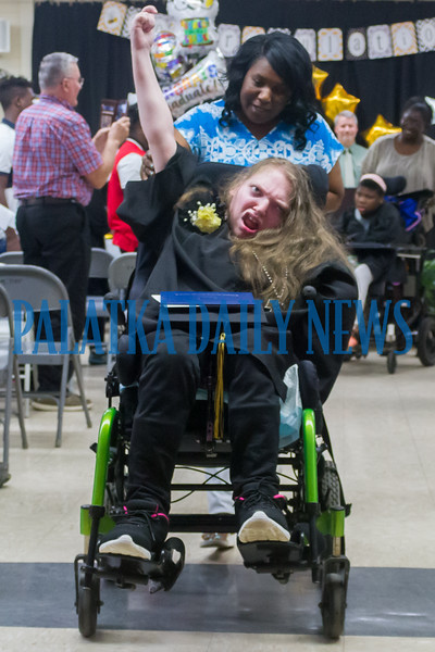 Graduate Christen Doane raises her hand as she rolls down the aisle after getting her diploma. Fran Ruchalski/Palatka Daily News