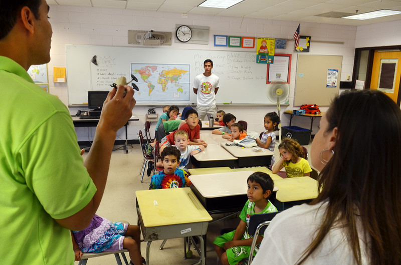 Teacher Javier Garary shows an example of the toy race car youngsters were tasked with building at engineering camp at Maple Glen Elementary School.    Monday,  July  7, 2014.   Photo by Geoff Patton