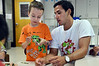 Teacher Ricardo Princ helps a youngster with his project  at engineering camp at Maple Glen Elementary School.    Monday,  July  7, 2014.   Photo by Geoff Patton