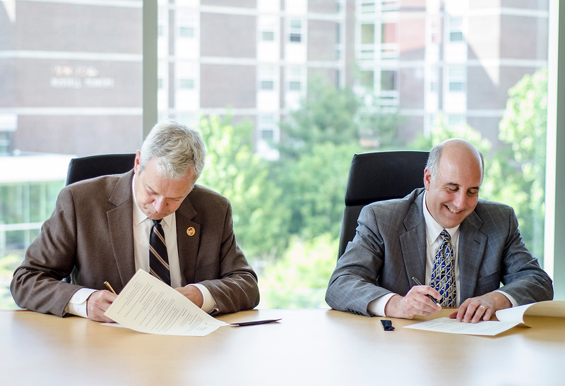 Superintendent of Schools Andre Ravenelle and Fitchburg State University President Richard Lapidus during the signing of the updated Honors Compact between the university and the high school. The new compacat re-ups the agreement originally signed in fall 2013 that brought  Fitchburg High honors students in for dual enrollment courses and other campus activities. SENTINEL & ENTERPRISE / Ashley Green