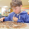 Ryan Kittredge, 10, counts out some change in his classroom at Fall Brook Elementary School on Tuesday morning. Christine Lay's fifth grade class at Fall Brook Elementary School in Leominster held a Coin War for a Cure, challenging other classes to raise money for the National Multiple Sclerosis Society. The school raised over $3,000. SENTINEL & ENTERPRISE/JOHN LOVE