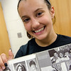 Fitchburg High senior Katherine Pawlak shows off her dad Michael Pawlak's yearbook in the alumni records room at FHS. SENTINEL & ENTERPRISE / Ashley Green