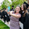 Nora Ann Papageorgiou jumps in line to snap a photo with best friend since first grade Alyssa Bartholomew during the 120th commencement ceremony at Fitchburg State University on Saturday afternoon. SENTINEL & ENTERPRISE / Ashley Green