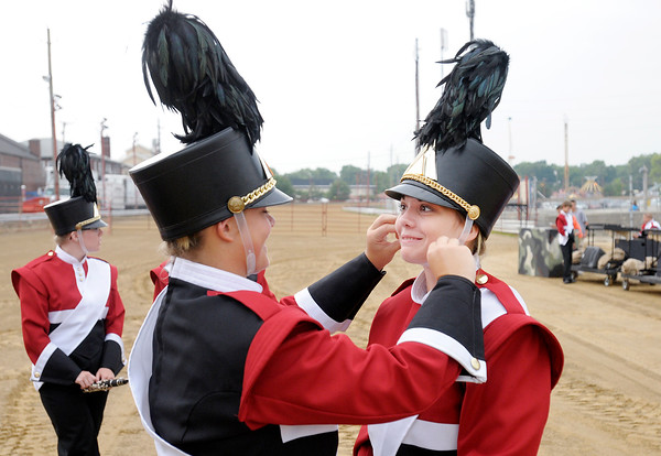 Don Knight | The Herald Bulletin<br /> Annie Gates helps Sydnee Eldridge adjust her chin strap as Frankton waits to compete during State Fair Band Day competition on Saturday.