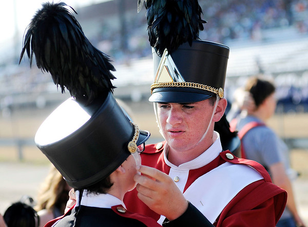 Don Knight | The Herald Bulletin<br /> Elijah Hahn helps Austin Sigler adjust his hat the Marching Eagles wait to perform during Indiana State Fair Band Day on Saturday.