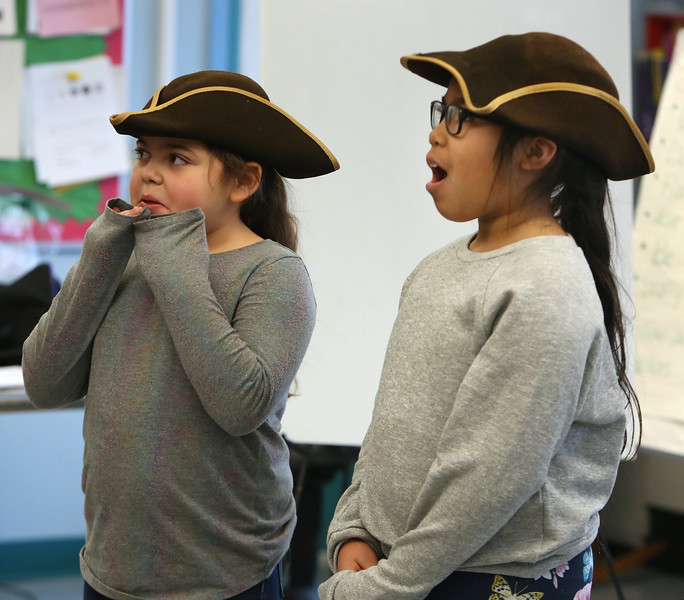 Freedom Trail Scholars Program visits McAuliffe Elementary School for a program reenacting events that led up to the Revolutionary War. Third graders Sophia Santiago, left, and Aleyna Rosario, right, listen to instructions for their role as colonists. (SUN/Julia Malakie)