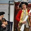Freedom Trail Scholars Program visits McAuliffe Elementary School for a program reenacting events that led up to the Revolutionary War. From left, third graders Jacoby Gonzalez and Duvan Duque, playing British soldiers, and Zack Reardon as Captain Thomas Preston, the commander at the Boston Massacre. (SUN/Julia Malakie)