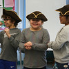 Freedom Trail Scholars Program visits McAuliffe Elementary School for a program reenacting events that led up to the Revolutionary War. Third graders, from left, Tomas Morales, Sophia Santiago, and Aleyna Rosario, play colonists pelting British soldiers with rocks. (SUN/Julia Malakie)