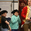Freedom Trail Scholars Program visits McAuliffe Elementary School for a program reenacting events that led up to the Revolutionary War. From left, third graders Duvan Duque, Jacoby Gonzalez and Gisele Rodrigues, playing British soldiers, and Zack Reardon as Captain Thomas Preston, the commander at the Boston Massacre. (SUN/Julia Malakie)