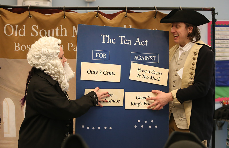 Freedom Trail Scholars Program visits McAuliffe Elementary School for a program reenacting events that led up to the Revolutionary War. Arielle Kaplan portraing loyalist Rev. Mather Byles, left, and Zack Reardon protraying Sam Adams, put up arguments for and against the Tea Act. (SUN/Julia Malakie)