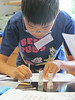 Sean Park, a Germantown Academy science camper, studies forensic evidence to help solve the mystery of the cookie their June 14. Montgomery Media staff photo / ERIC DEVLIN