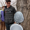 Greater Lowell Tech students tap sugar maples to collect sap to make maple syrup, as part of their environmental science class. Alex Rodriguez, 17, a senior from Lowell, watches sap drip from a just installed tap. (SUN/Julia Malakie)