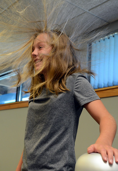 Lauren Atchley's hair stands up as she touches a Van Der Graff Generator with children conducting experiments in Physical Science & Eelectricity during the GSK Science in Summer event at the Perkasie Branch of the Free Library of Bucks County on Tuesday July 22,2014.Photo by Mark C Psoras/The Reporter