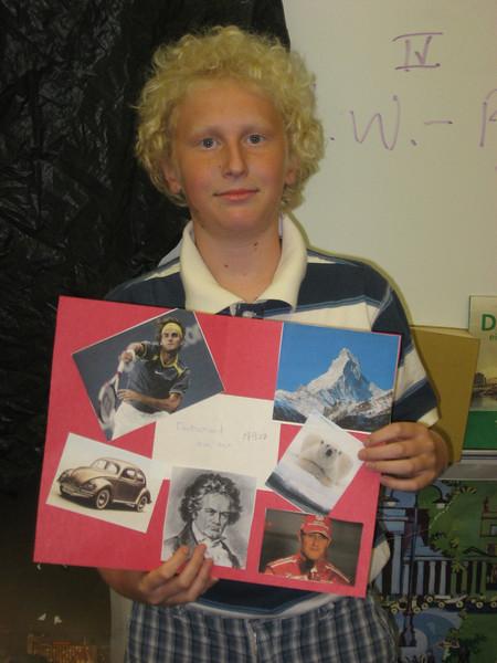 Erich H ist stolz auf sein Poster/Collag von beruehmten deutschspraechigen Personen. Deutsch I, im Herbst 2007.