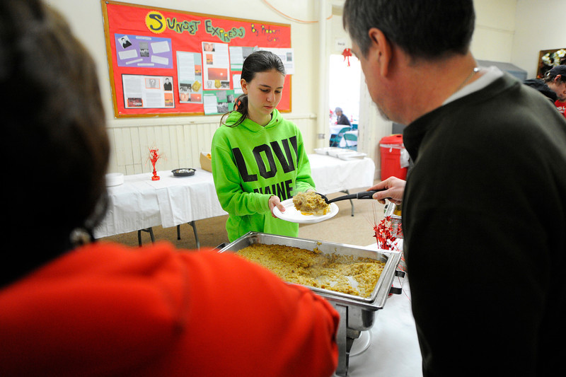 Senior Brianna Debella, 18, of Lunenburg receives food during Goodrich Academy's annual holiday dinner at the Fitchburg school, Thursday.<br /> SENTINEL & ENTERPRISE / BRETT CRAWFORD