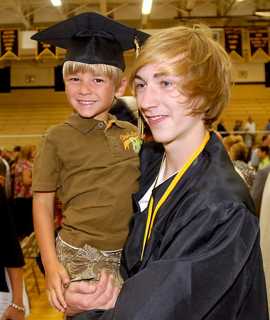 Daleville High School graduate Spencer Badgley poses for family pictures with his cousin Dominic Bertram, 5.