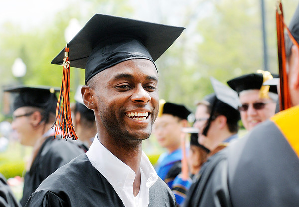 Don Knight | The Herald Bulletin<br /> Ralf Etienne smiles as graduates file past their professors during the processional during Anderson University's 98th commencement on Saturday.