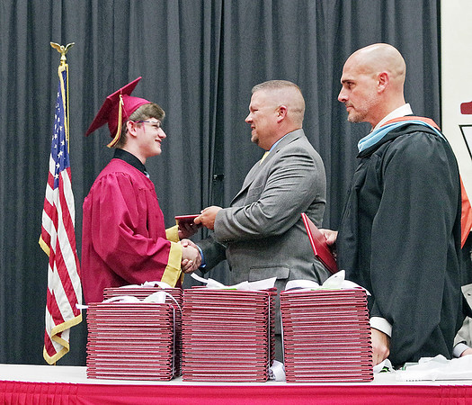 Mark Maynard | for The Herald Bulletin<br /> School Board President Kyle Williams, assisted by Alexandria High School Principal Tom Johns, presents Graduating Senior Michael Carney with his diploma.