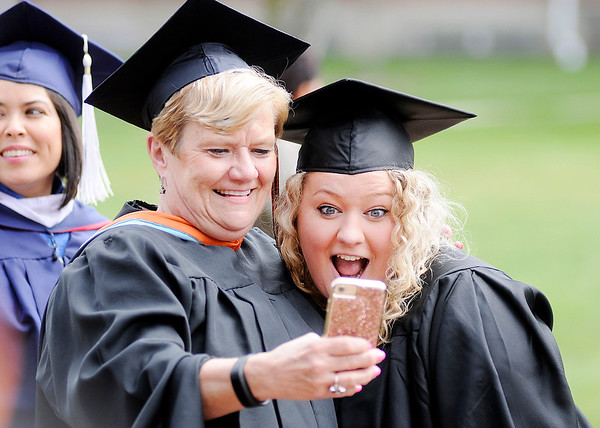 Don Knight | The Herald Bulletin<br /> A professor poses for a selfie with a student during the precession at Anderson University's 99th Commencement on Saturday.
