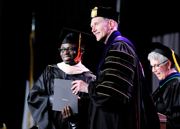Don Knight   The Herald Bulletin<br /> Zakiyou Sounkere accepts his Master of Business Administration degree from Anderson University President John Pistole during AU's 99th Commencement on Saturday.