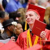 Don Knight | For The Herald Bulletin<br /> A graduate shows off his new diploma as he walks back to his seat during Anderson High School's graduation on Tuesday.