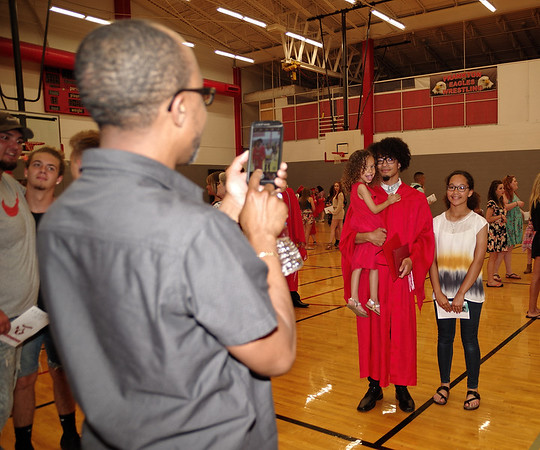 Proud father KIrby Wheeler snaps a photo of his newly-graduated son, Kelby, posing with his sisters, Kiara and Koral, after Frankton High School commencement.